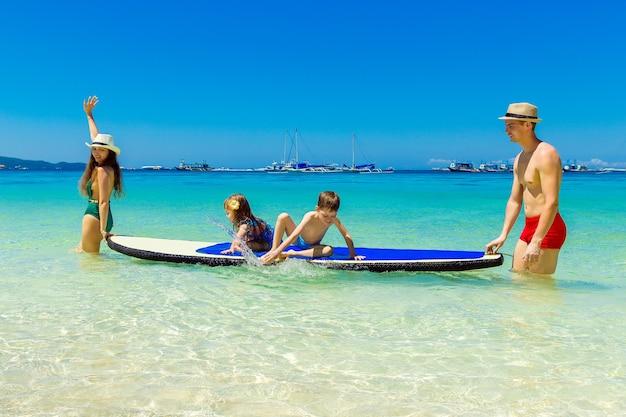 Happy familymom papa petite fille et garçon s'amuser sur une planche à pagaie dans la mer tropicale