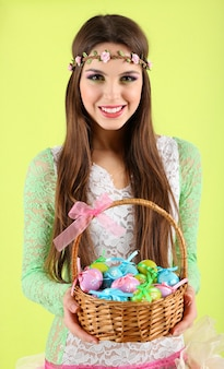 Happy female holding panier avec des oeufs de pâques, sur fond vert