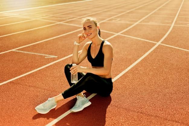 Happy fit woman in sportwear écouter de la musique avec des écouteurs et tenant une bouteille d'eau alors qu'il était assis sur une piste de stade avec revêtement rouge en plein air