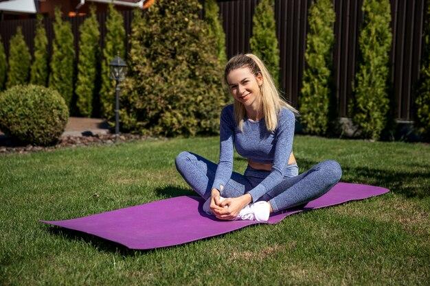 Happy fitness sportive femme assise sur un tapis rose au jardin avec de l'herbe verte fraîche près de house