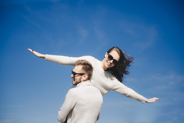 Happy girl and guy running et hugging in flight against the sky, travel love story concept, selective focus