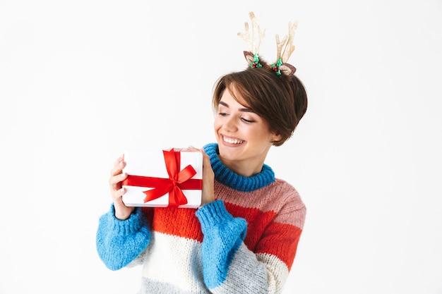Happy girl gaie portant chandail debout isolé sur blanc, tenant la boîte présente