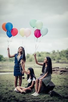 Happy girl girl friends tenant des ballons multicolores