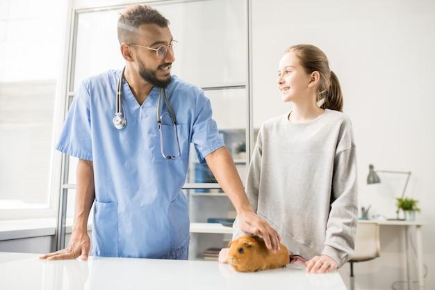 Happy girl in casualwear parlant au vétérinaire tout en consultant ses soins de santé de cobaye