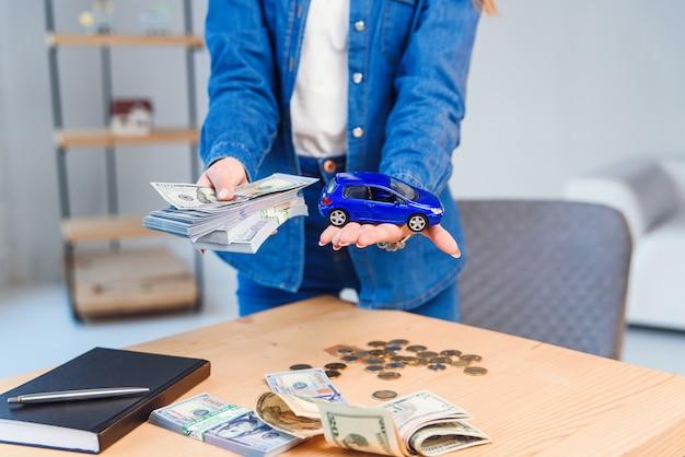 Happy girl in eyeglasses détient une somme d'argent dans une main et un petit modèle de sa future voiture dans une autre main.
