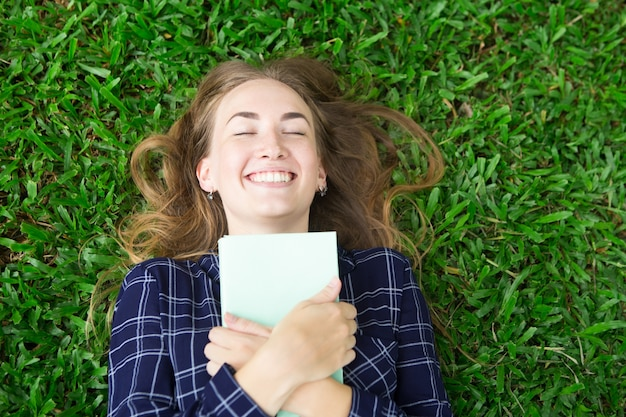 Happy girl lying on grass et embracing book