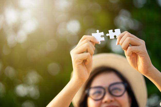 Happy girl montrant deux puzzles.l'amour complet.