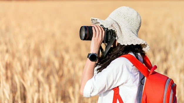 Happy girl photographier champ de blé d'orge mûr dans la douce lumière du coucher du soleil