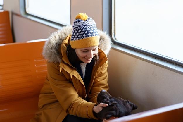 Happy girl porter des vêtements d'hiver assis dans un train local à parler avec son beau chien voyageant ensemble