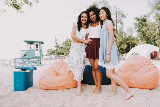 Happy girls hug beach party sac chaises sur le sable.