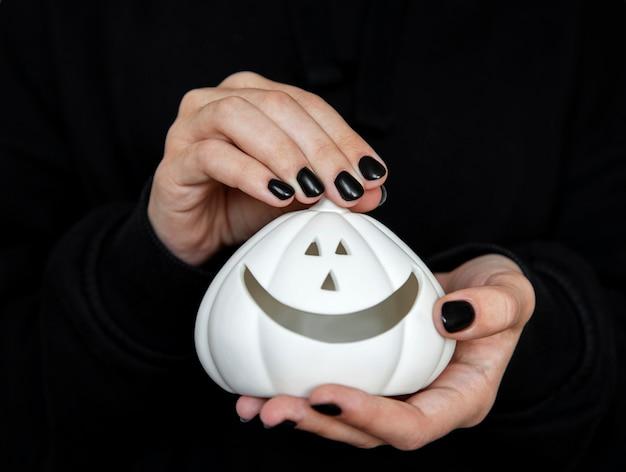 Happy halloween female mains tenant des citrouilles drôles sur fond noir