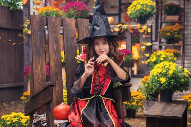 Happy halloween girl en costumes de sorcière s'amusant à l'automne près de la maison
