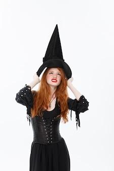 Happy halloween sexy cheveux roux sorcière avec son chapeau magique volant au-dessus de sa tête. isolé sur fond blanc