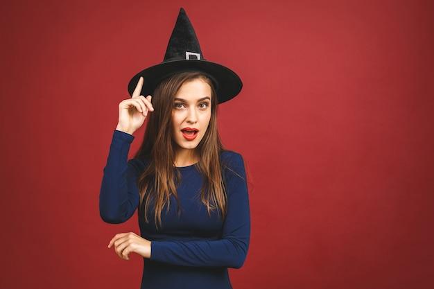 Happy halloween witch avec un maquillage lumineux et des cheveux longs. belle jeune femme surprise posant en costume sexy de sorcières. isolé sur fond rouge.