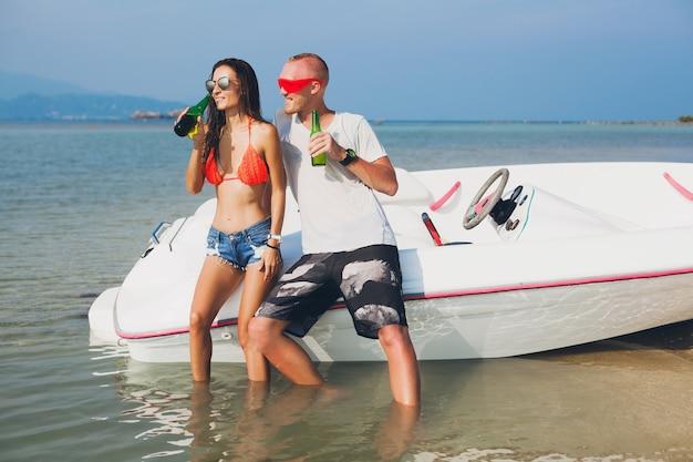 Happy hipster femme et homme buvant de la bière en vacances tropicales d'été en thaïlande voyageant en bateau en mer, fête sur la plage, les gens s'amusent ensemble, émotions positives