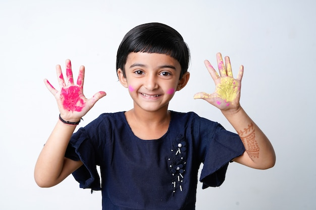 Happy holi greeting - mignonne petite fille indienne avec des mains colorées, isolé sur fond blanc