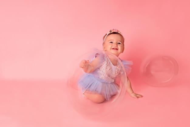 Happy kid girl avec des ballons sur fond rose célèbre son premier anniversaire