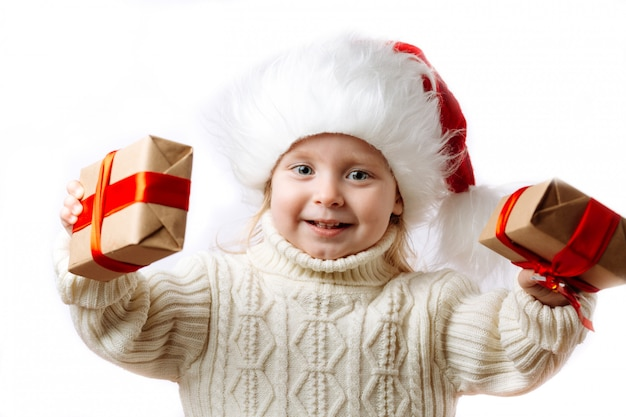 Happy kid in santa hat hold christmas gift boxes