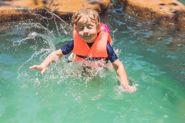 Happy kid saute dans l'étang soulevant beaucoup de spray sur une journée ensoleillée