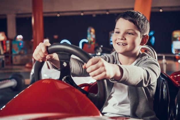 Happy kid sittng dans la voiture de jouet dans le centre d'amusement