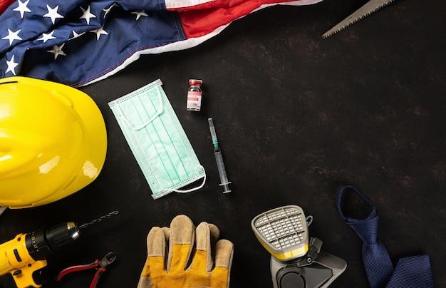 Happy labor plusieurs outils de travail de constructeur d'ingénieurs masque médical protecteur et drapeau américain
