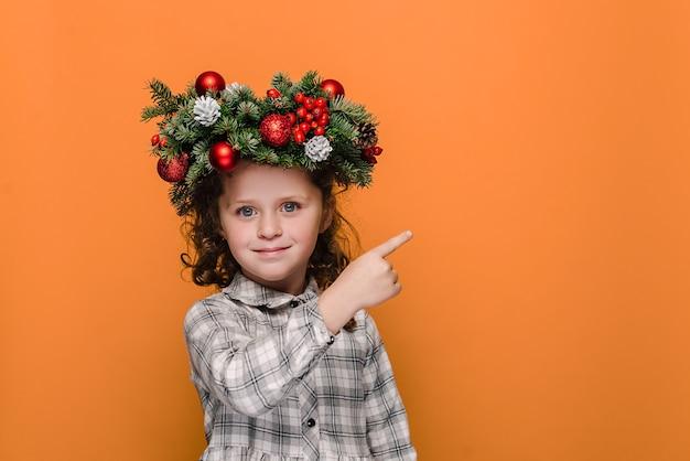 Happy little kid girl points avec l'index sur un espace libre pour le contenu publicitaire