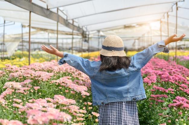 Happy little traveller sur le jardin de fleurs de chrysanthèmes