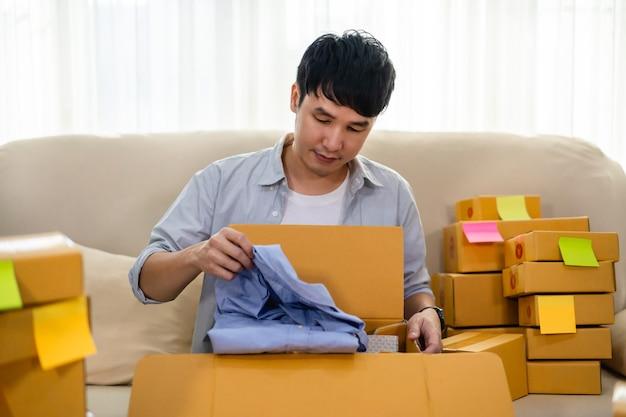Happy man boîte à colis en carton ouvert dans le salon à la maison, achat sur boutique en ligne