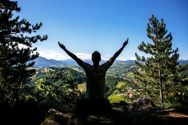 Happy man a levé les mains devant une belle vallée verdoyante dans les montagnes. concept émotionnel de style de vie de voyage