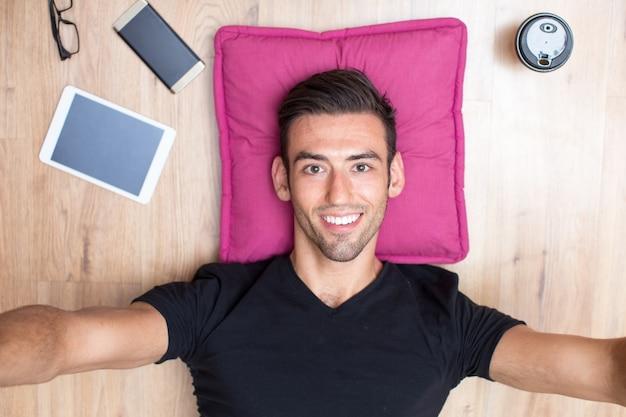 Happy man mentir sur le plancher et prendre selfie photo