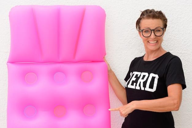 Happy mature nerd woman holding matelas pneumatique et debout isolé