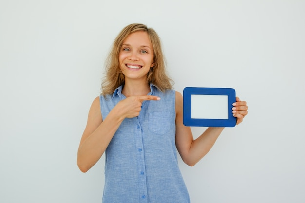 Happy nice lady pointing at empty picture frame