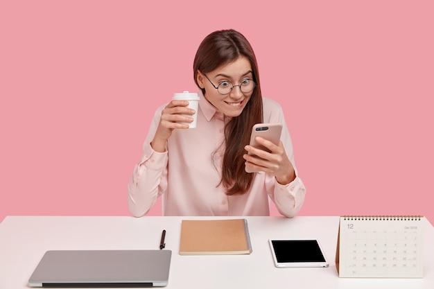 Happy office worker détient un téléphone portable, lit des nouvelles positives sur la page web tout en naviguant sur internet, porte des lunettes à la mode, a un ordinateur portable, une tablette