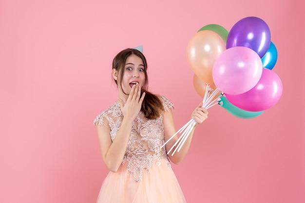 Happy party girl avec chapeau de fête tenant des ballons mettant la main à sa bouche sur rose