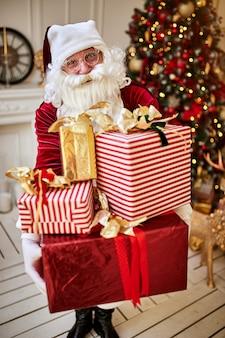 Happy santa claus a apporté de nombreux cadeaux aux enfants.