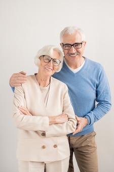 Happy senior couple affectueux avec des sourires à pleines dents sur mur blanc debout
