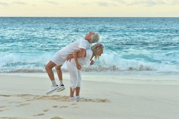 Happy senior couple exerçant en été au bord de la mer