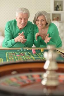 Happy senior couple jouant avec des jetons de casino