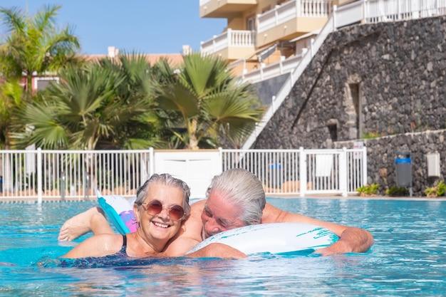 Happy senior couple nager dans la piscine en jouant avec matelas gonflable. heureux retraités profitant des vacances d'été et du soleil