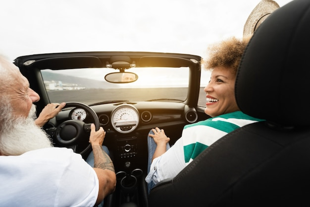 Happy senior couple s'amusant dans une voiture décapotable pendant les vacances d'été - focus sur le visage de la femme