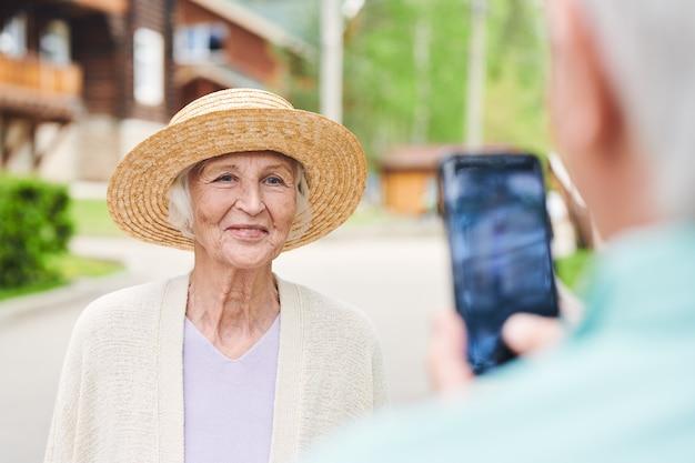 Happy senior female in élégant chapeau de paille posant debout devant son mari en prenant une photo sur smartphone