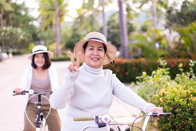 Happy senior femme asiatique à vélo avec sa fille au parc,