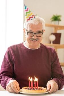 Happy senior man making anniversaire souhait tout en regardant des bougies allumées sur un gâteau fait maison