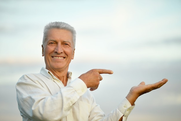 Happy senior man pointant sur fond de ciel