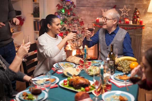Happy senior man trinquant un verre de vin avec sa fille à la fête de famille de noël.