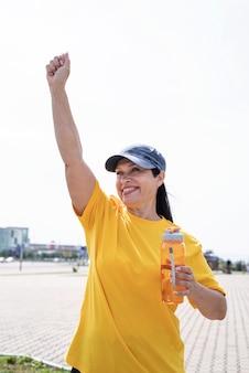 Happy senior woman dans des vêtements de sport exerçant dans le parc debout avec les bras vers le haut
