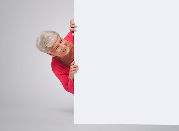 Happy senior woman derrière le tableau blanc