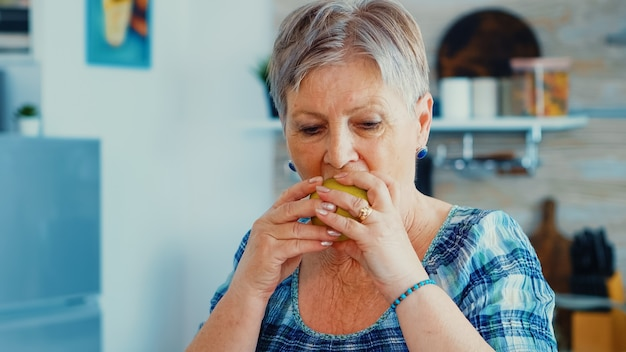 Happy senior woman eating pomme verte saine dans la cuisine pendant le petit déjeuner. heureux mode de vie biologique frais avec de la bonne nourriture. portrait authentique positif gai