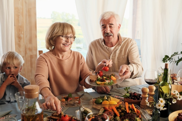 Happy senior woman putting légumes sur l'assiette de son mari alors qu'ils étaient assis à la table pendant le dîner de vacances