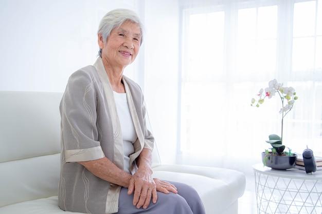 Happy senior woman relaxing on canapé à la maison dans le salon.